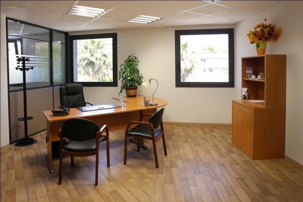 Un bureau dans une pièce claire disposant de deux grandes fenêtres.