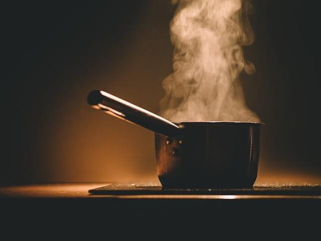 Une casserole fume sur une table de cuisson.
