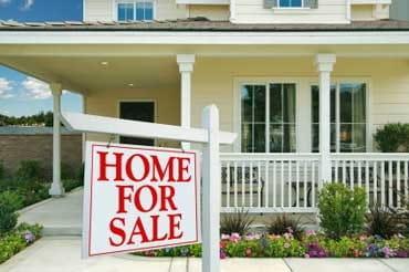 """Photographie d'une maison avec le panneau """"À vendre"""" en anglais."""