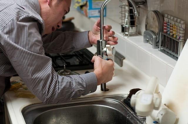 Plombier en train de réparer un robinet.