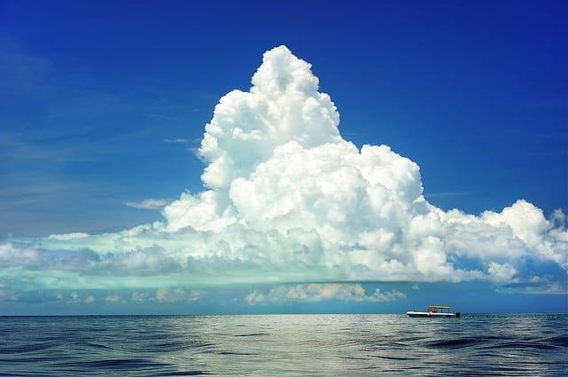 Un bateau sur une mer calme, sur fond de ciel bleu et de nuages blancs.