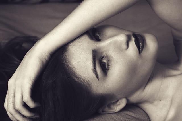 Femme allongée, photo en noir et blanc.