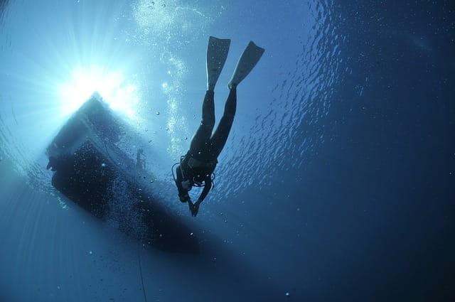 Plongeur en combinaison de plongée et palmes, nageant sous un bateau, dans l'eau.