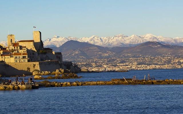 Vue de la ville d'Antibes depuis la mer donnant sur des monts enneigés.