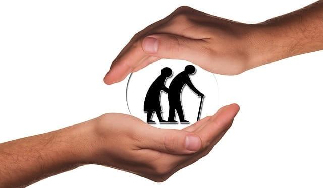 Bulle de personnes âgées en maison de retraite, protégée par deux mains