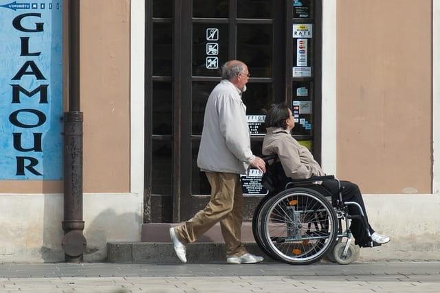 Personne en fauteuil roulant dans la rue.