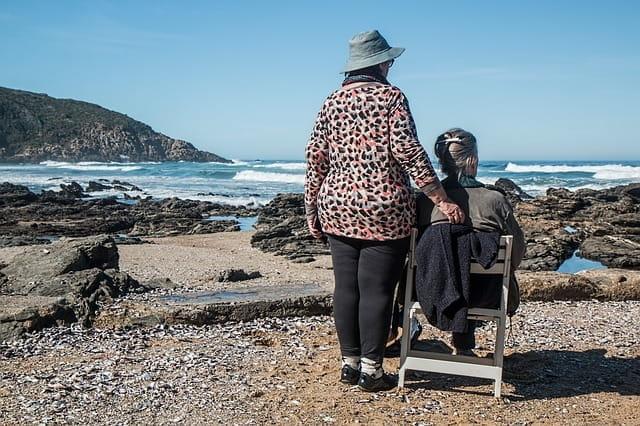 Deux personnes âgées qui regardent la mer au bord d'une plage.