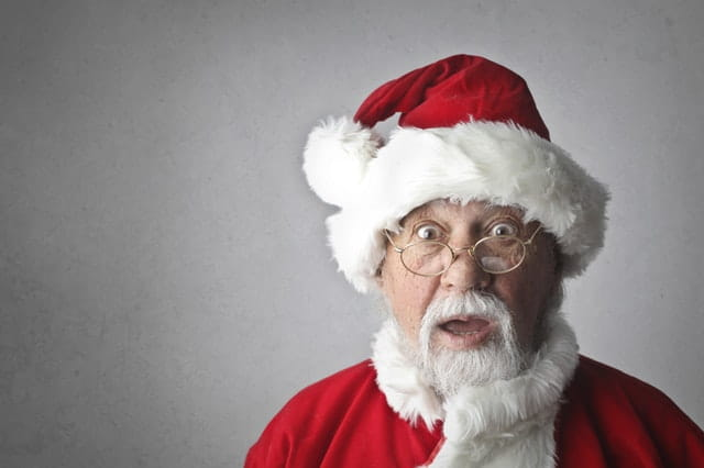 Père Noël étonné de voir des cadeaux insolites.