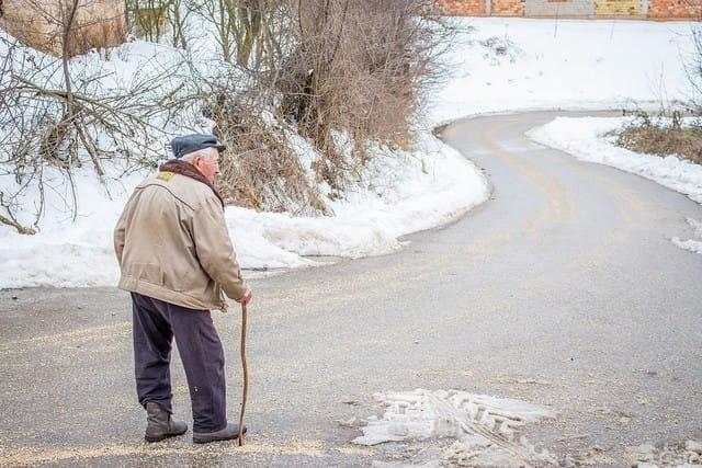 Personne âgée marchant avec une canne.