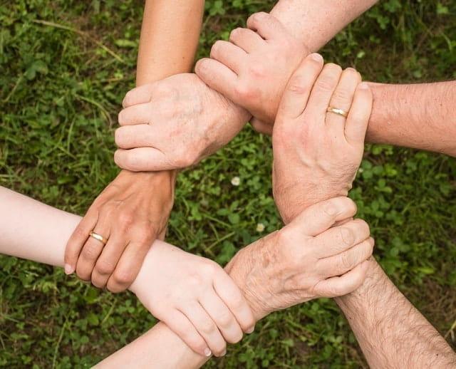 Ronde de mains de personnes de tout âge et type.