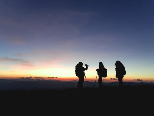 Silhouettes de personnes en montagne.